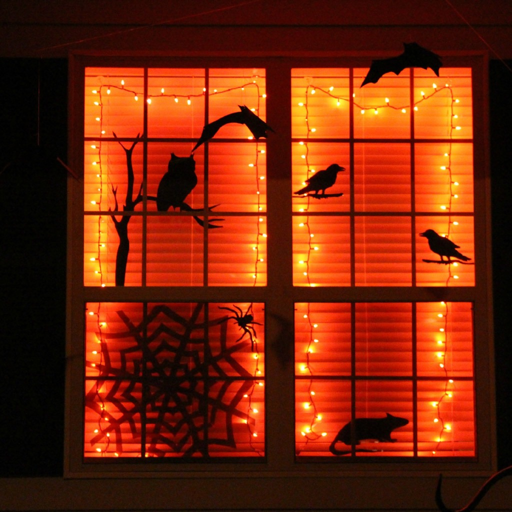 Orange strinng lights attached to a window frame with Halloween window decals