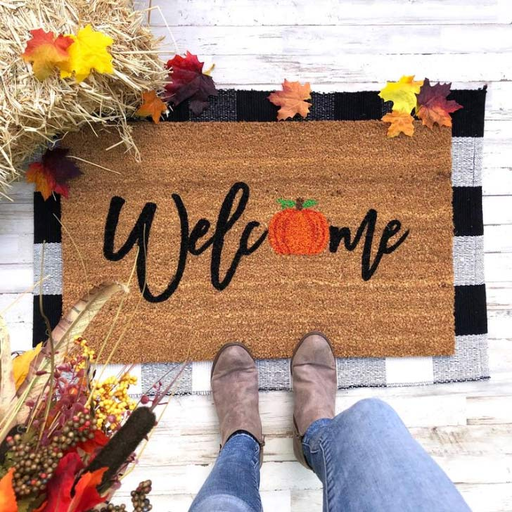 welcome door mat with a pumpkin